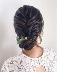 Lockere Brautfrisur gekordelt mit Blumenschmuck